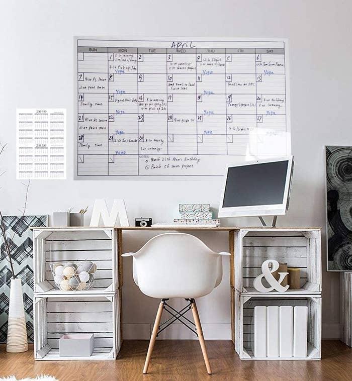 A large whiteboard calendar behind a desk