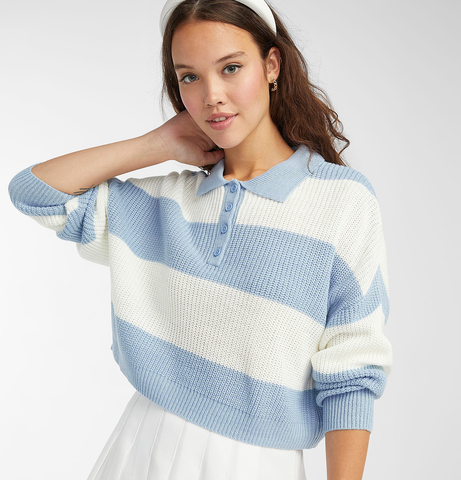 a person wearing the striped polo sweater with a skirt
