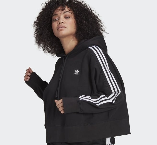 a person wearing the adidas hoodie with stripes down the sleeve