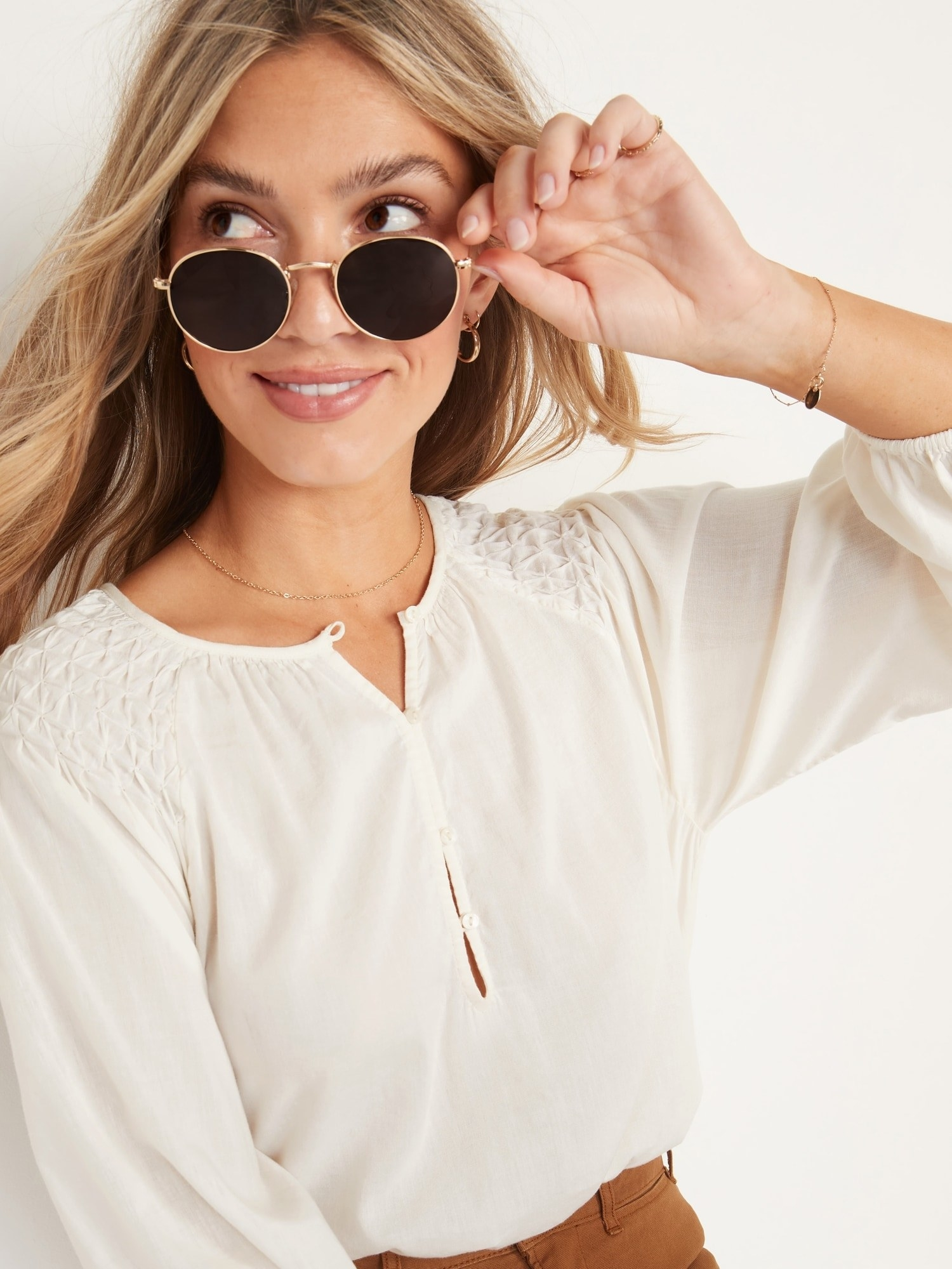 a person wearing the half-button up blouse while wearing a pair of sunglasses