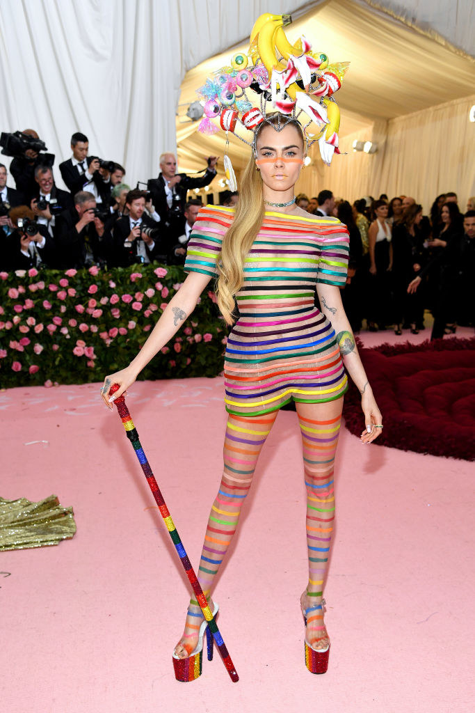 rainbow-striped body suit and a headband with dentures, bananas, and sparkly eyeballs
