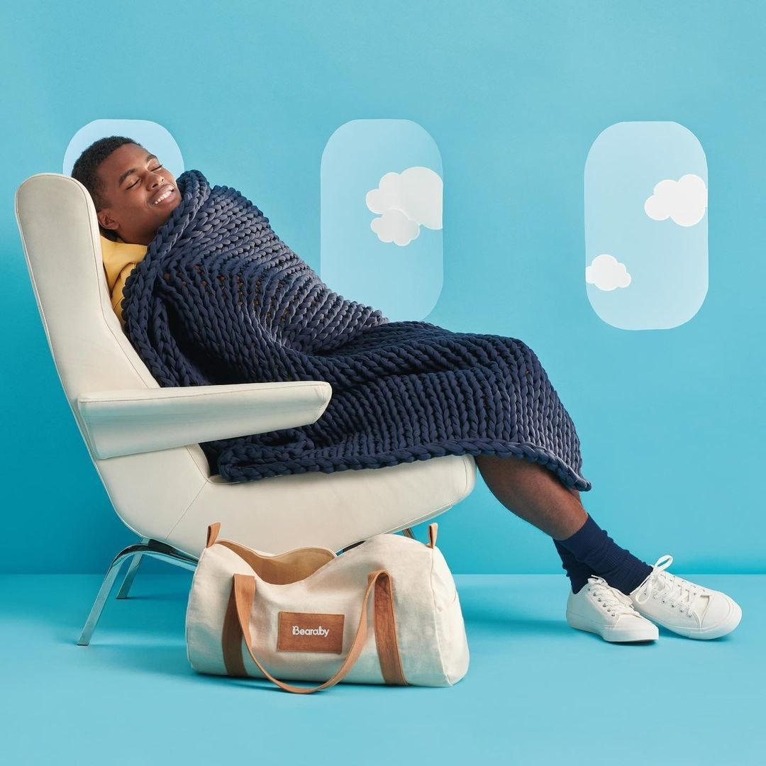 model sitting in a chair that looks like an airplane seat with a navy blue knitted blanket over them