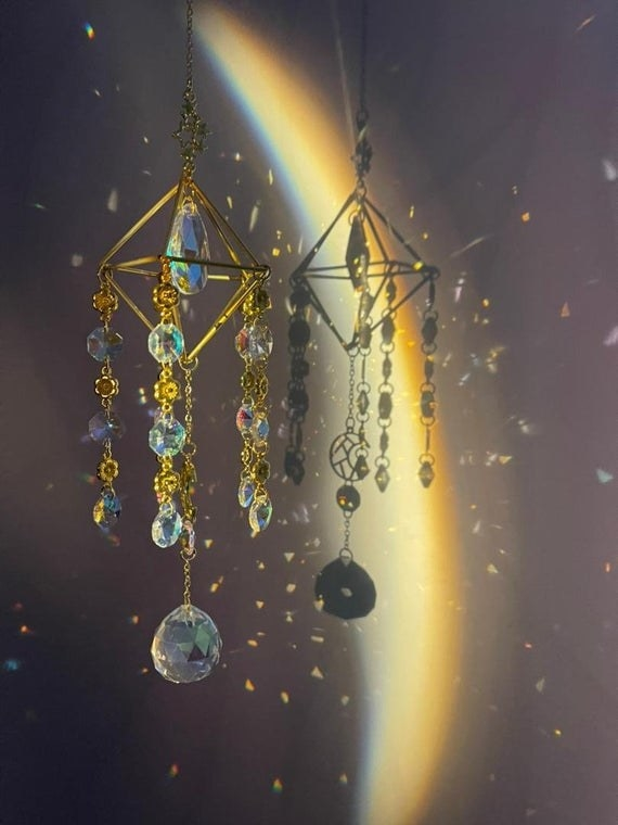 The crystal suncatcher is shown with light beams shining through it, casting many rainbows on the wall behind it