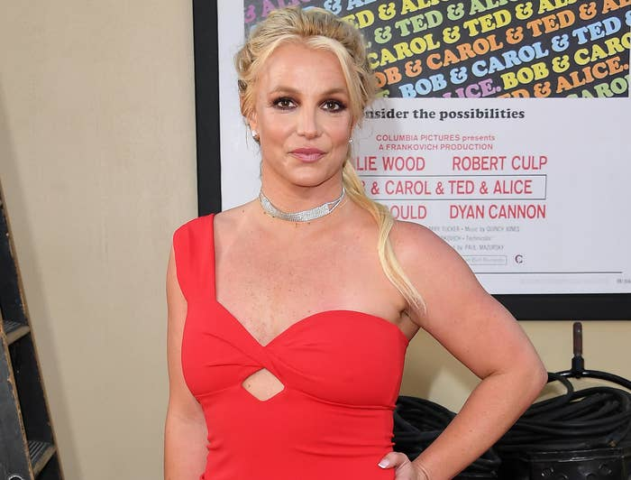Britney poses with her hand on her hip in a one shoulder red dress