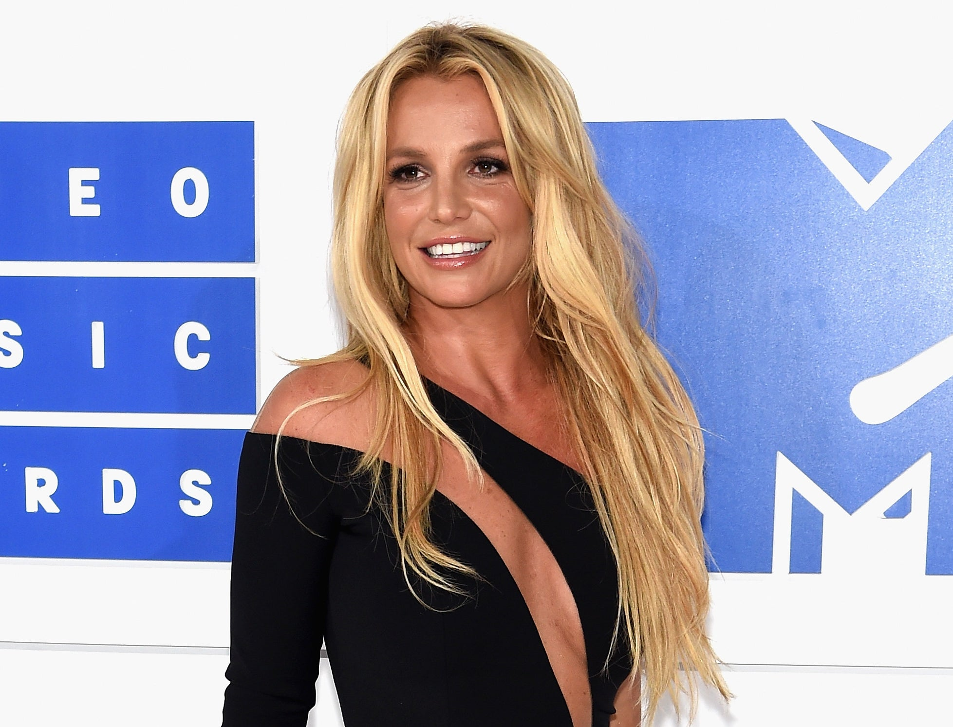 Britney wears a black one shoulder dress with a cut out design
