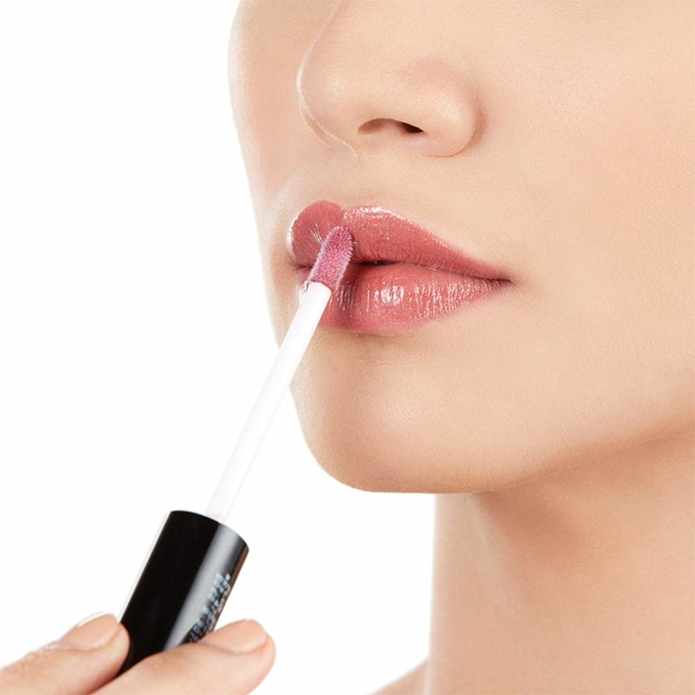 An image of a person applying lip gloss on her lips.