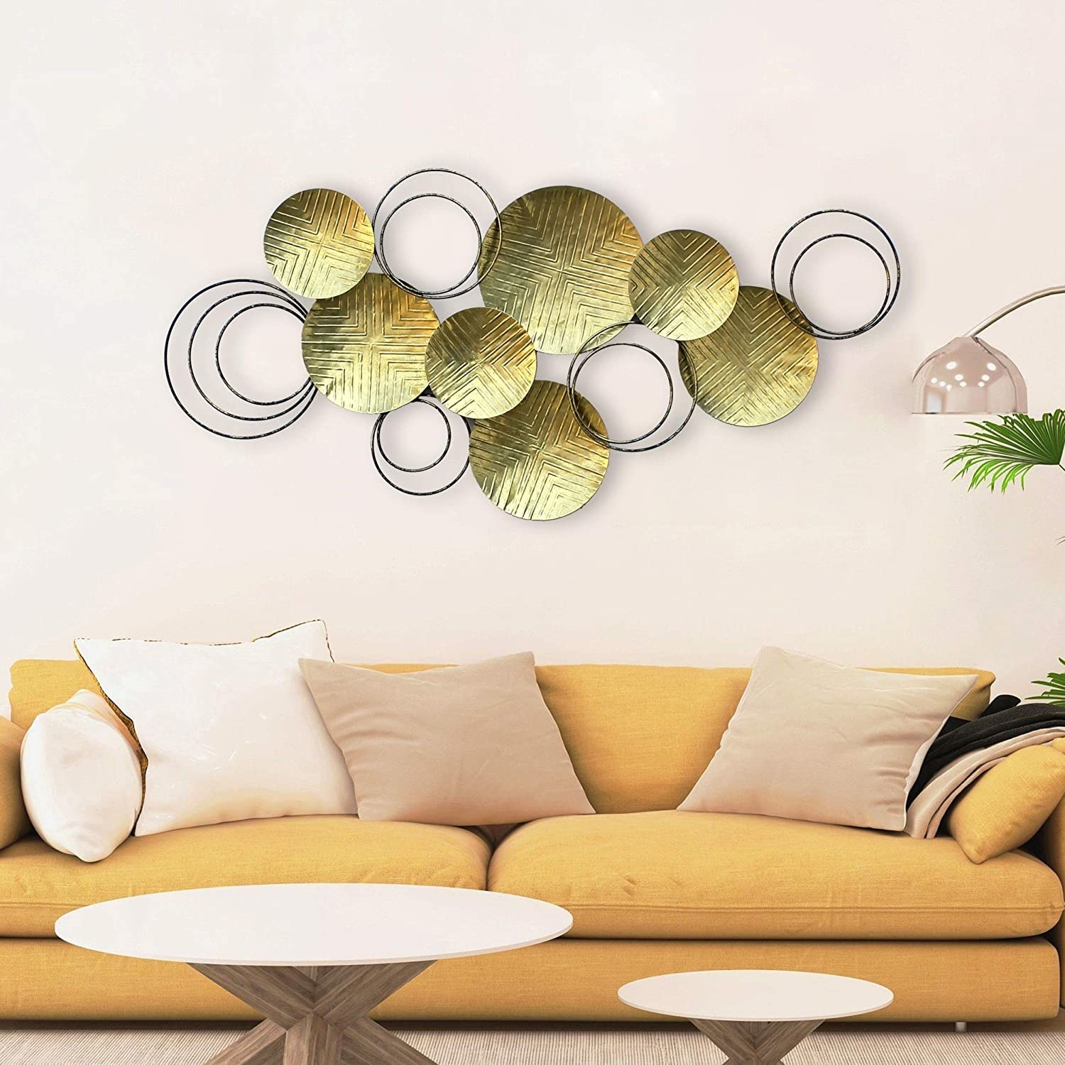 A metal wall art with several round gold metal plates and black wire circles clustered together