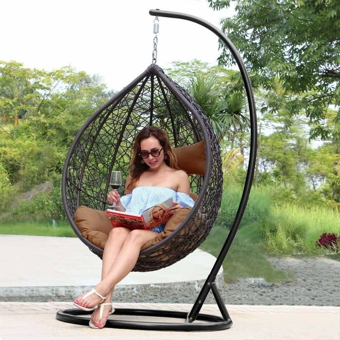 A woman sitting on the swing while having a drink and reading a magazine