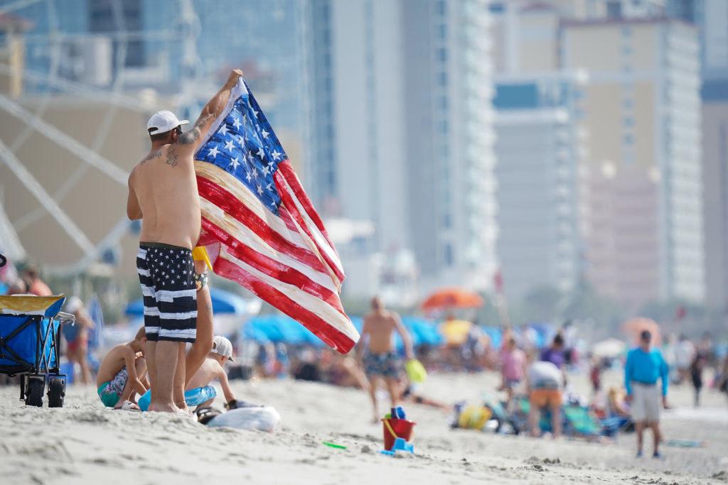 Guy raising an American flag on the beach