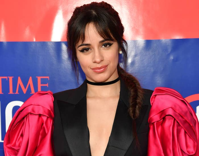 Camila wears a black dress with plunging neckline and red poofy sleeves