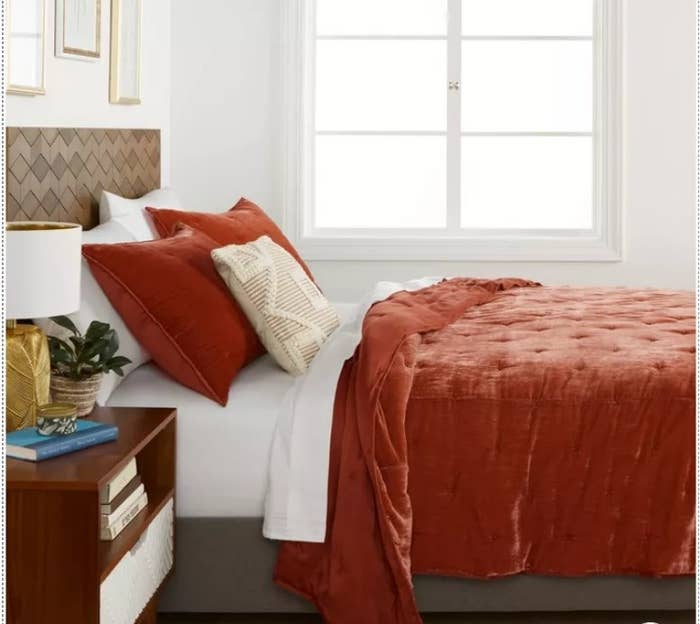 A red velvet quilt on a bed next to a wooden end table