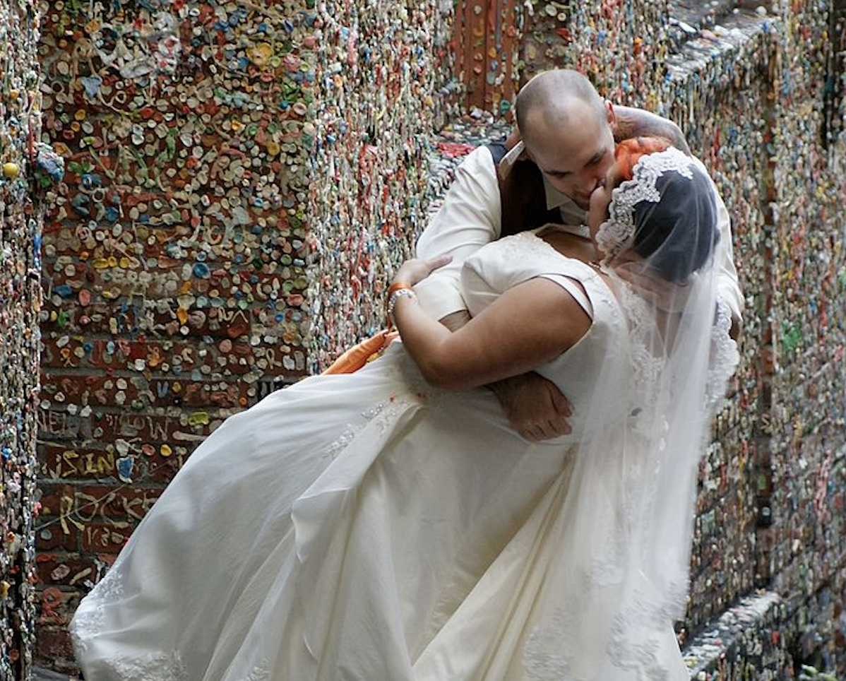 A newlywed couple kissing in front of the gum wall
