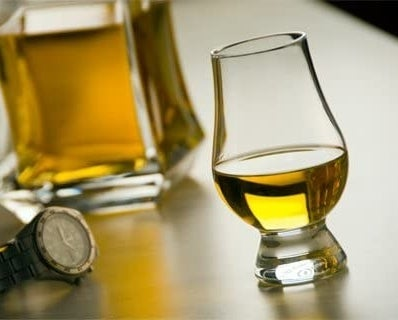 A single glencairn glass filled halfway with whiskey