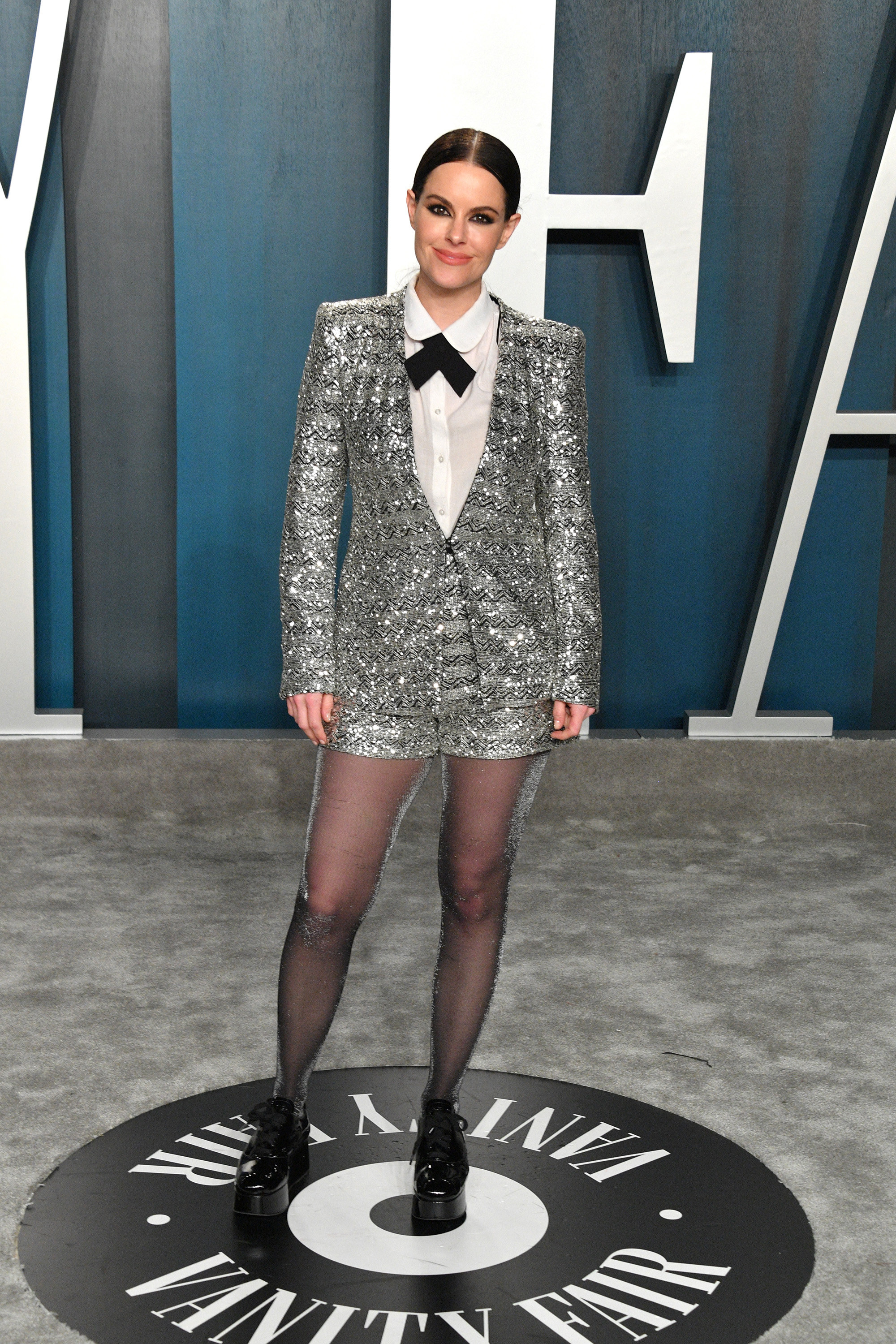 Emily posing at the Vanity Fair Oscar party in a sequined suit with matching shorts, tights, and platform ankle boots