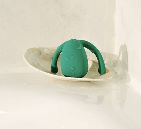 Wet green vibrator on bathtub ledge