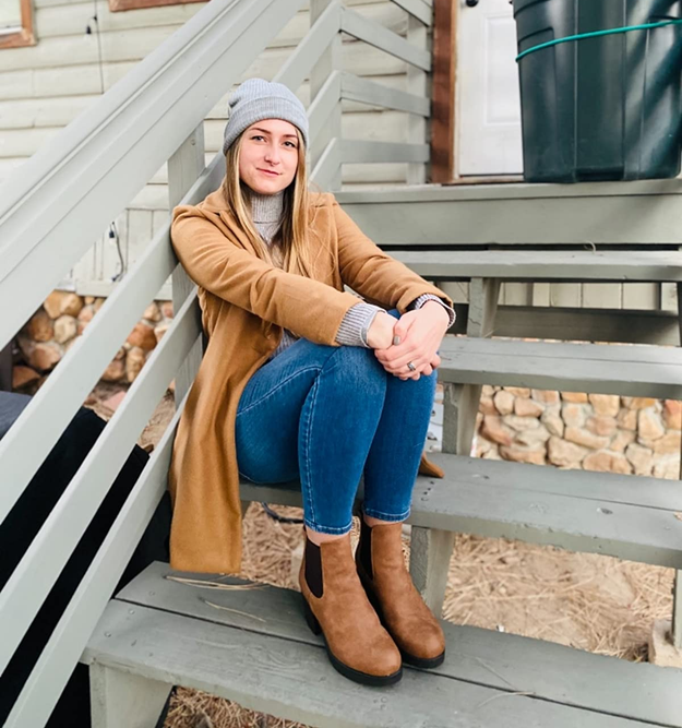 a reviewer sits on wooden stairs wearing chelsea boots
