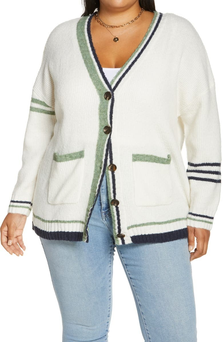 Model is wearing a white varsity-style cardigan with green lines around the hems and denim jeans
