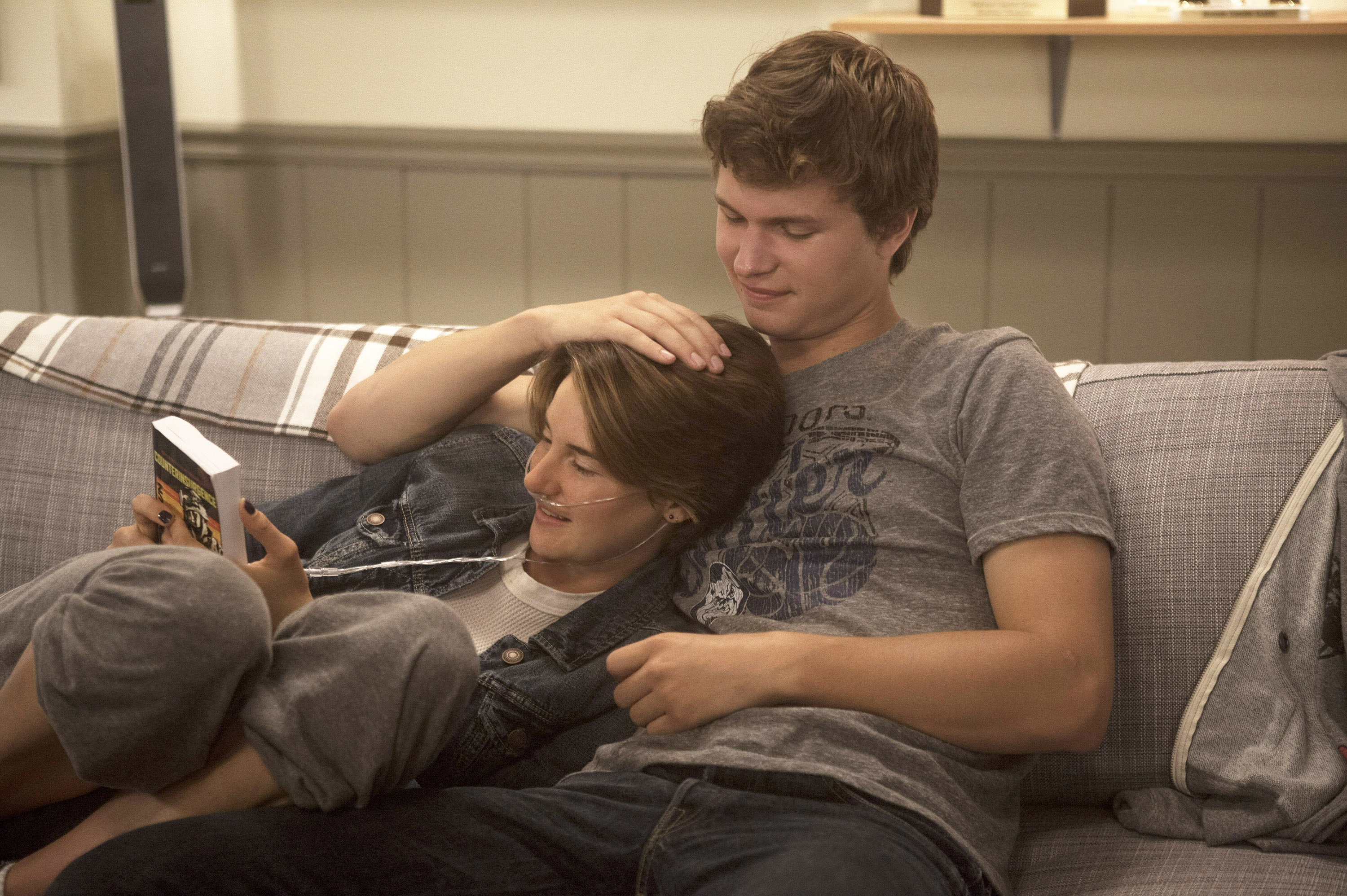 Shailene Woodley looking at a book while cuddling with Ansel Elgort
