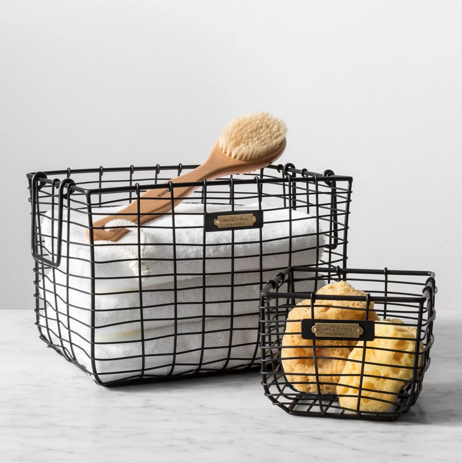two of the wire baskets one large version with a towel and scrubber and a smaller version with sponges in it