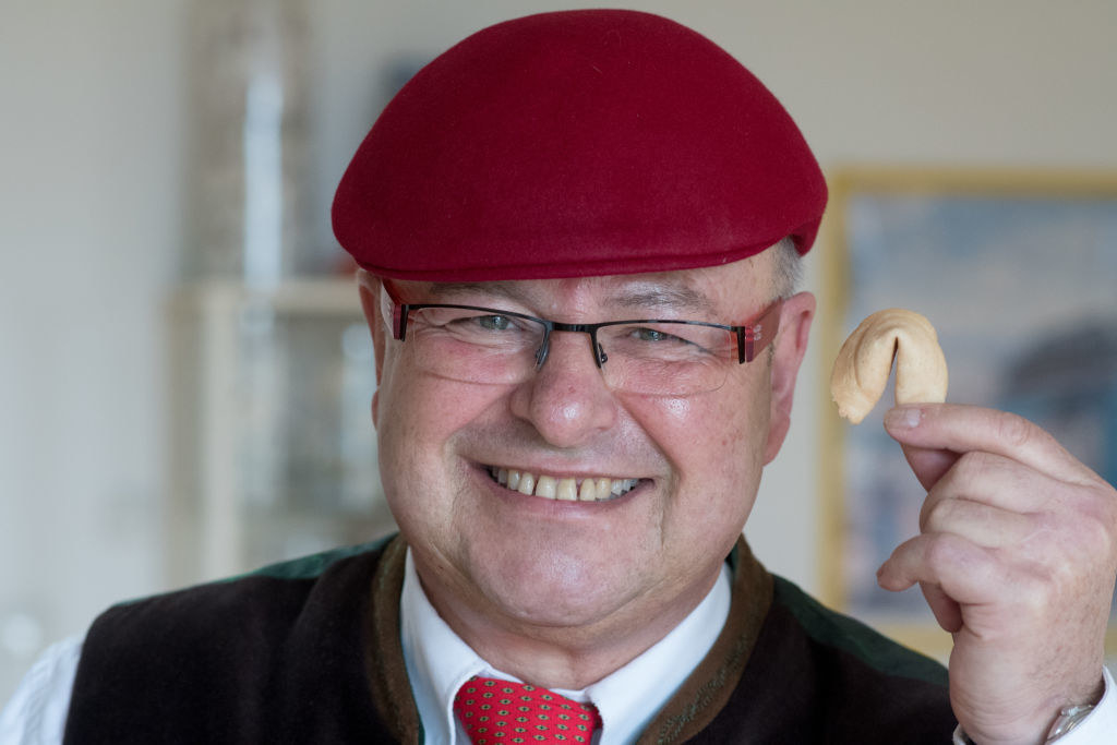 a man smiling and holding up a fortune cookie