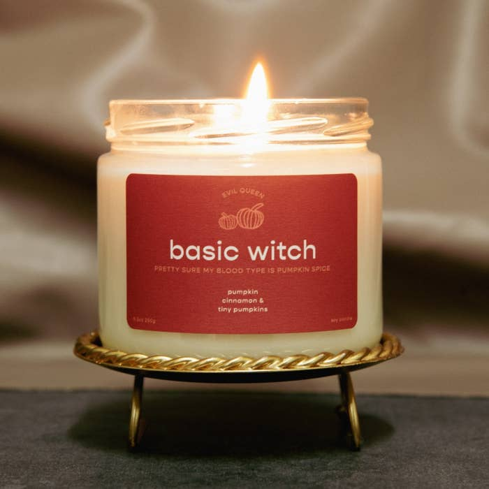 """a candle with an orange label on it that says """"basic witch, pretty sure my blood type is pumpkin spice"""""""