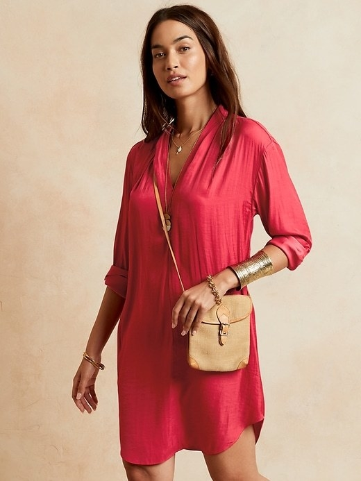 Model is wearing a red shift dress with a small beige crossbody bag and gold jewelry