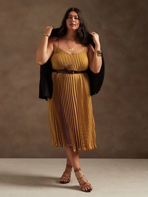 Model is wearing a gold satin pleated dress, gladiator sandals, and a black jacket