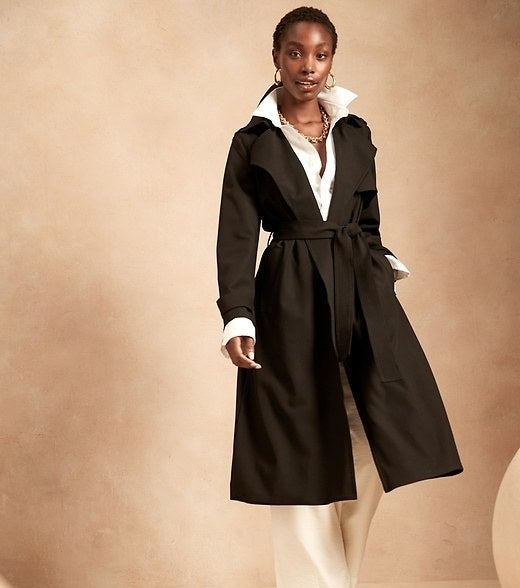 Model is wearing a black trench coat over a white top and cream trousers