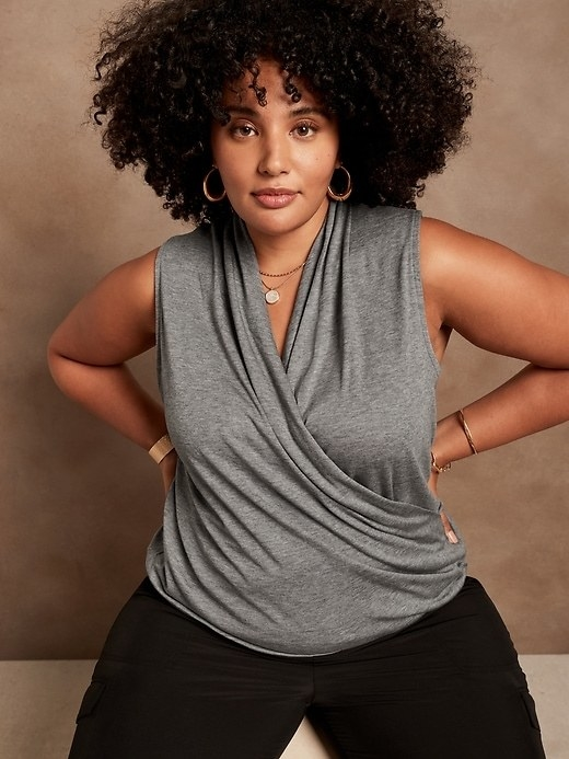 Model is wearing a grey sleeveless wrap top and black pants