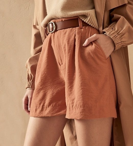 Model is wearing clay high waisted shorts, a beige sweater, and beige coat
