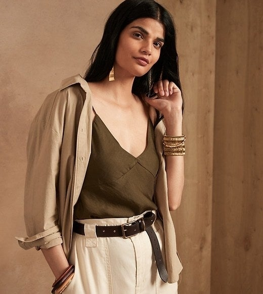 Model is wearing an olive green camisole, beige jacket, and cream trousers