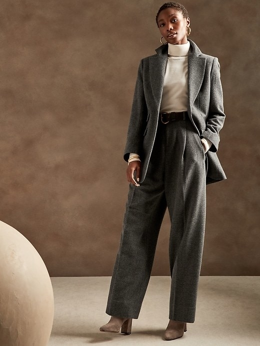 Model is wearing grey wool wide-leg pants, a matching blazer, and a white turtleneck sweater
