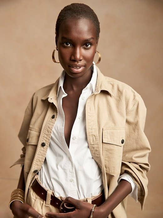 Model is wearing a white button down shirt with a beige jacket and beige pants
