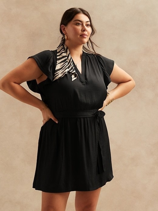 Model is wearing a black dress with a V-neckline and flutter sleeves