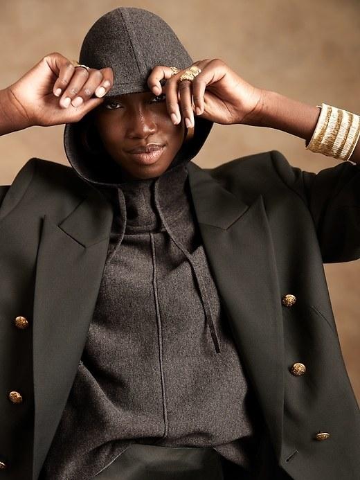 Model is wearing a dark grey hoodie under a black coat