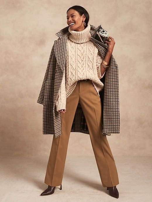 Model is wearing a dark tan trouser, cream sweater, and a gingham coat