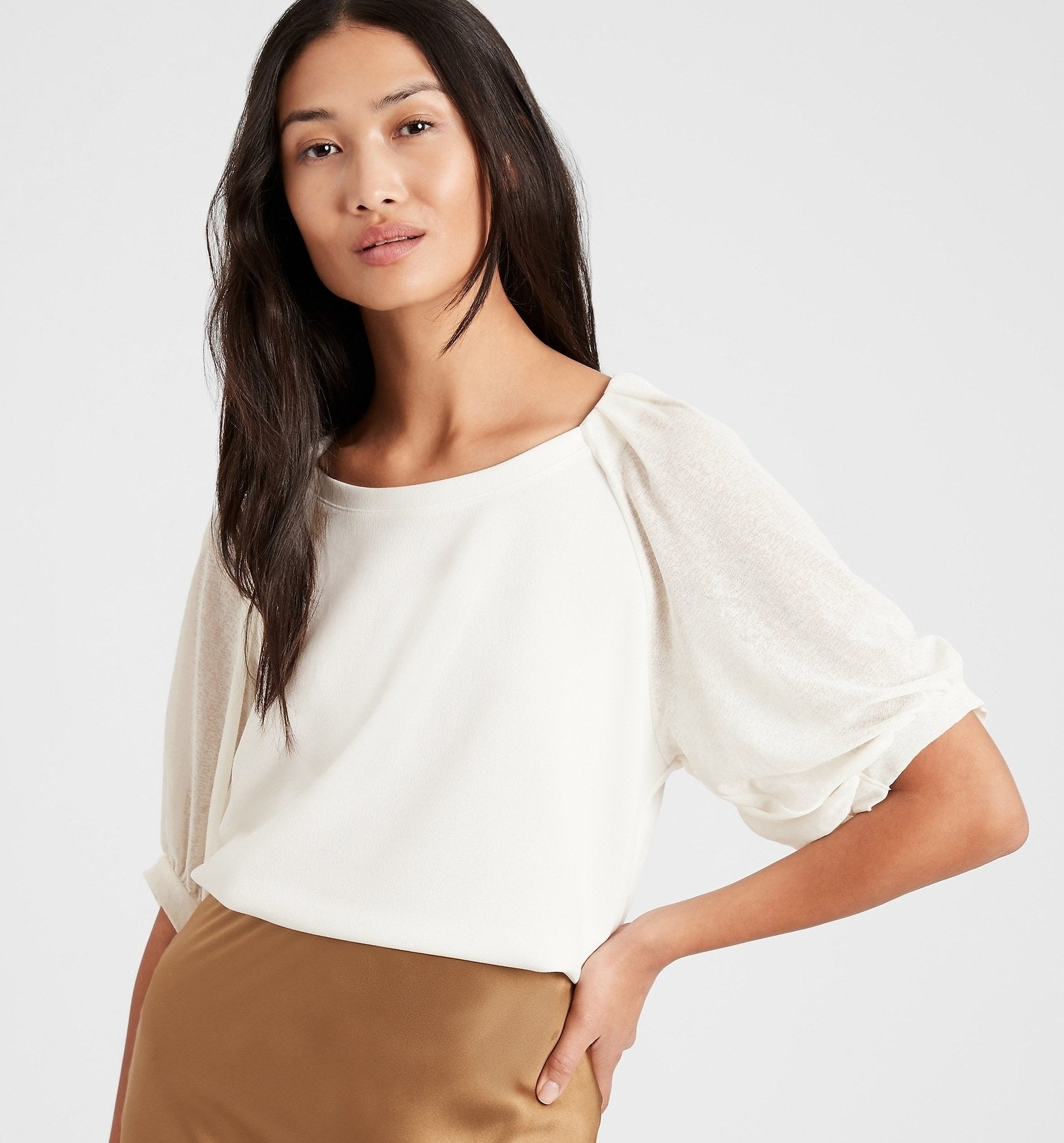 Model is wearing a white top with balloon sleeves and a tan skirt
