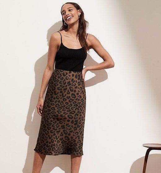 Model is wearing a leopard print midi skirt over a black tank top