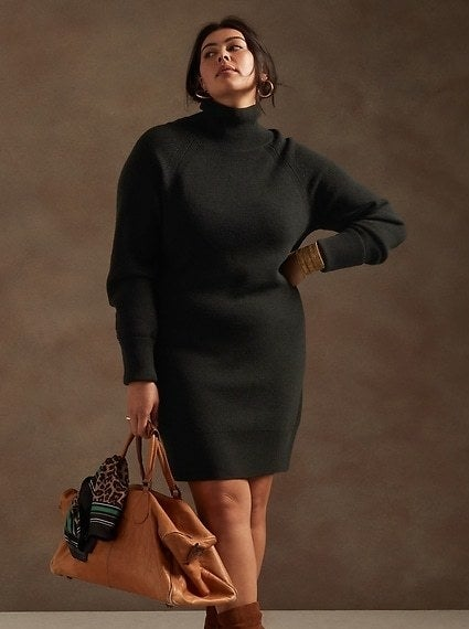 Model is wearing a black turtleneck sweater dress while holding a brown bag
