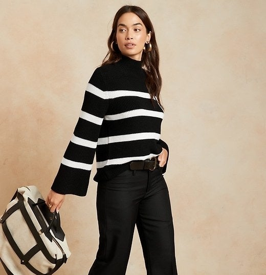 Model is wearing and black and white thick-striped sweater and black trousers