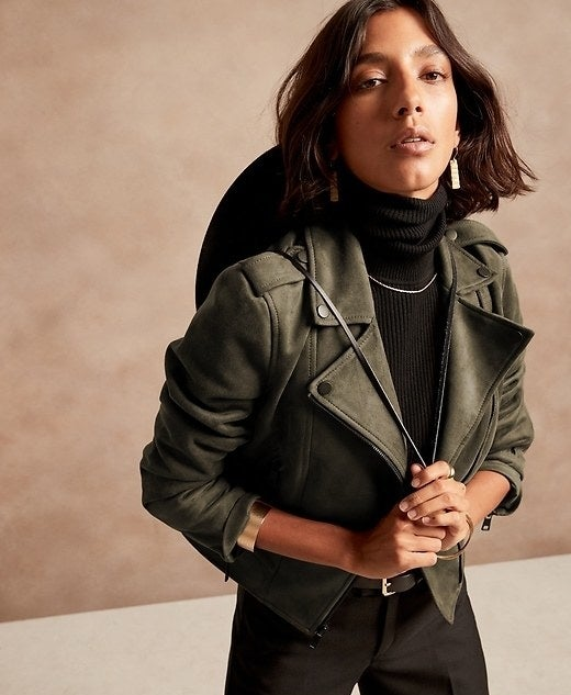 Model is wearing an olive green jacket, black top, and black pants