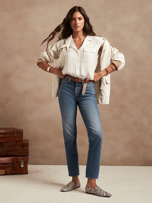 Model is wearing blue denim jeans with a white top and jacket and zebra print loafers