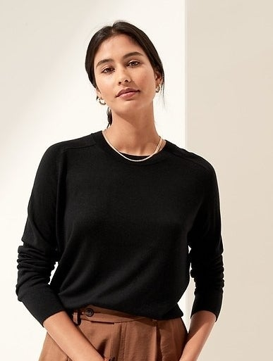 Model is wearing a black sweater and clay trousers