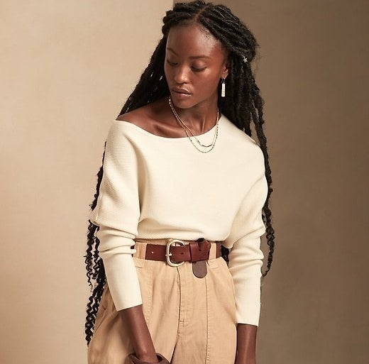 Model is wearing a cream sweater and beige trousers