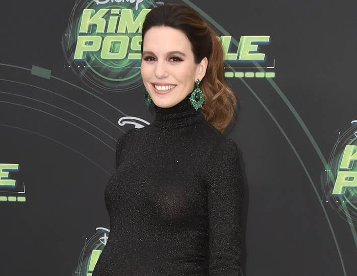 Christy wears a black long sleeve dress to a Kim Possible event