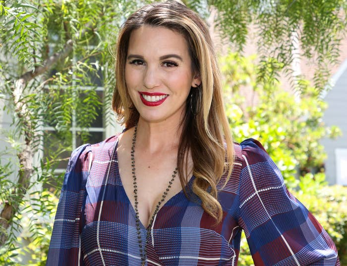 Christy smiles while wearing a blue and red plaid wrap dress