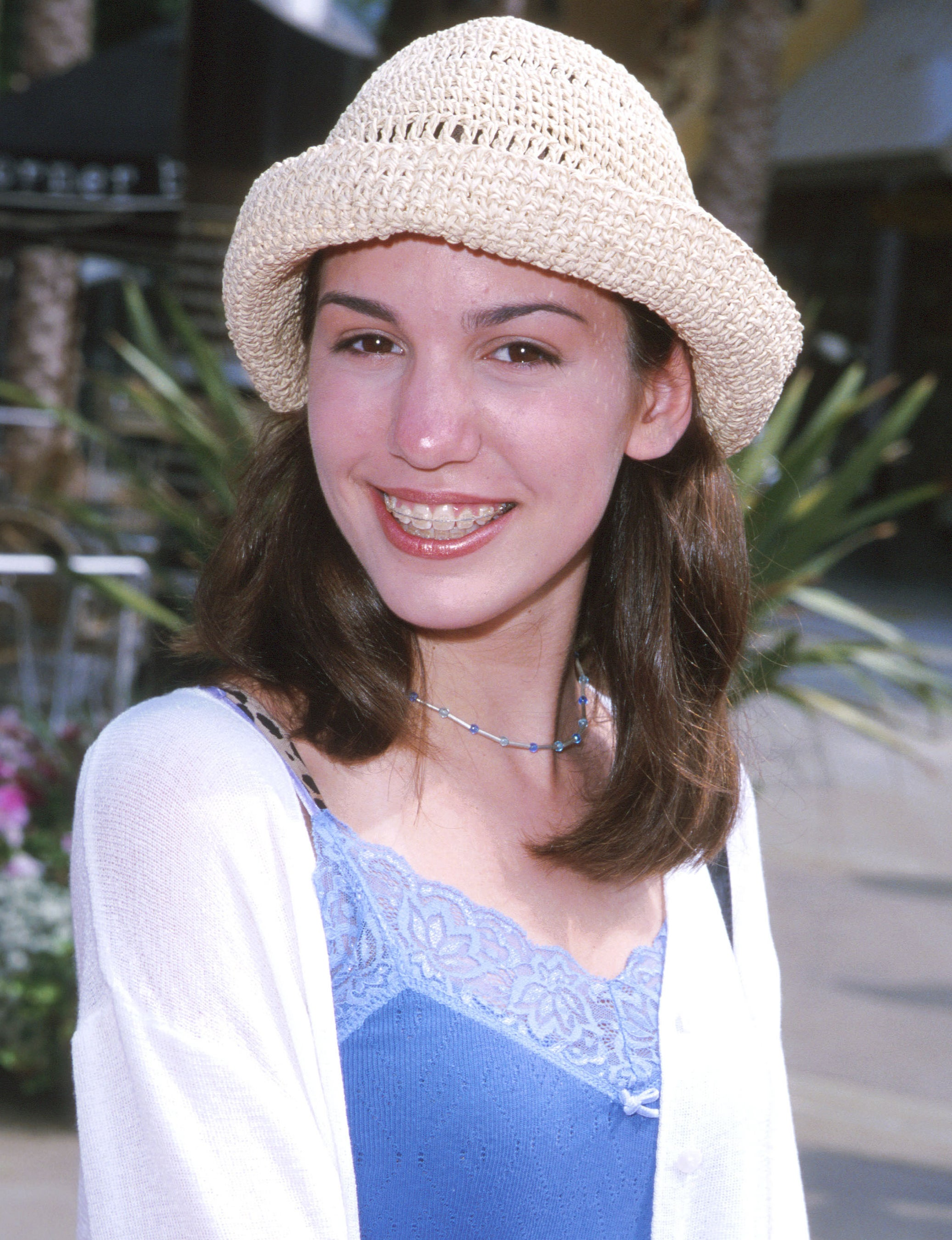 A youngChristy has braces and wears a straw hat