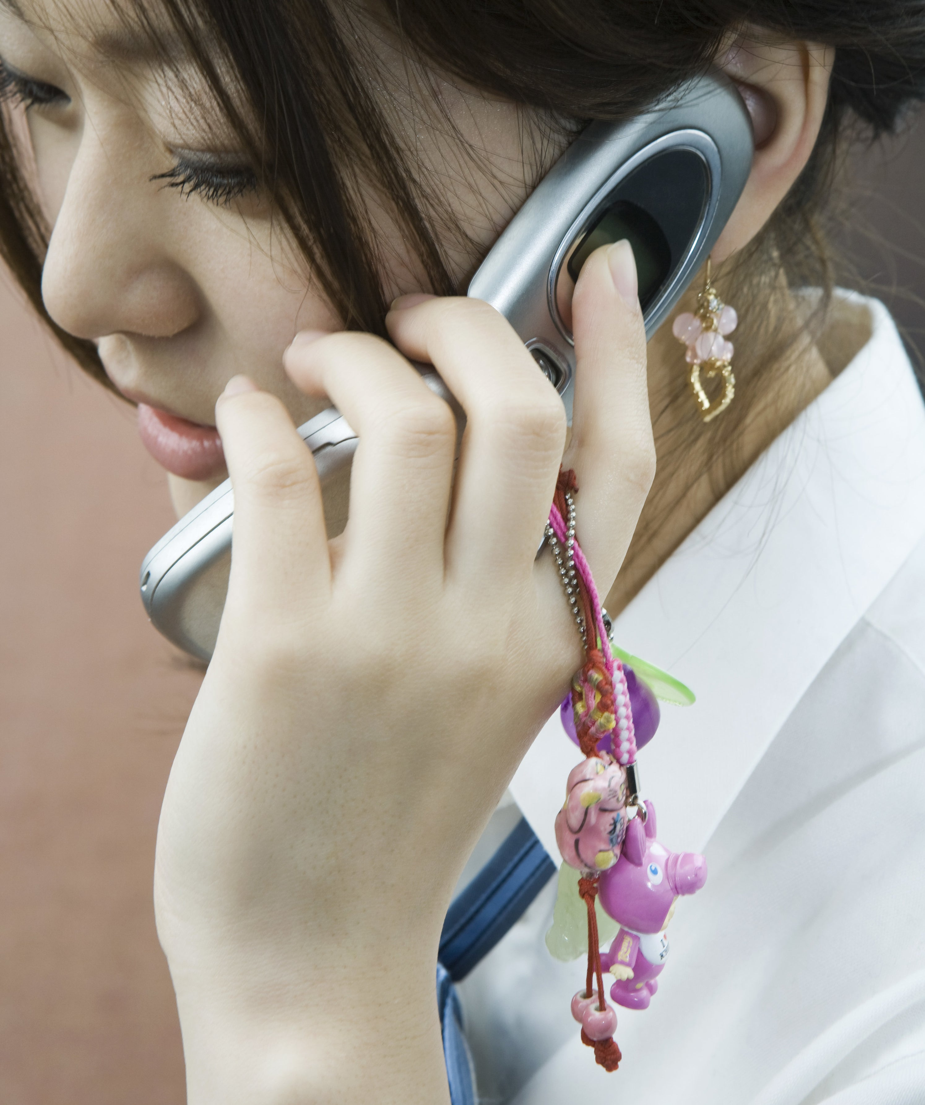Young woman using cellphone decorated with charms