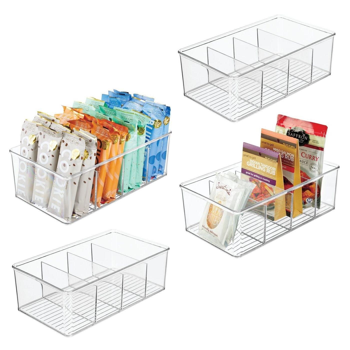 Four clear plastic storage bins with snacks organized inside