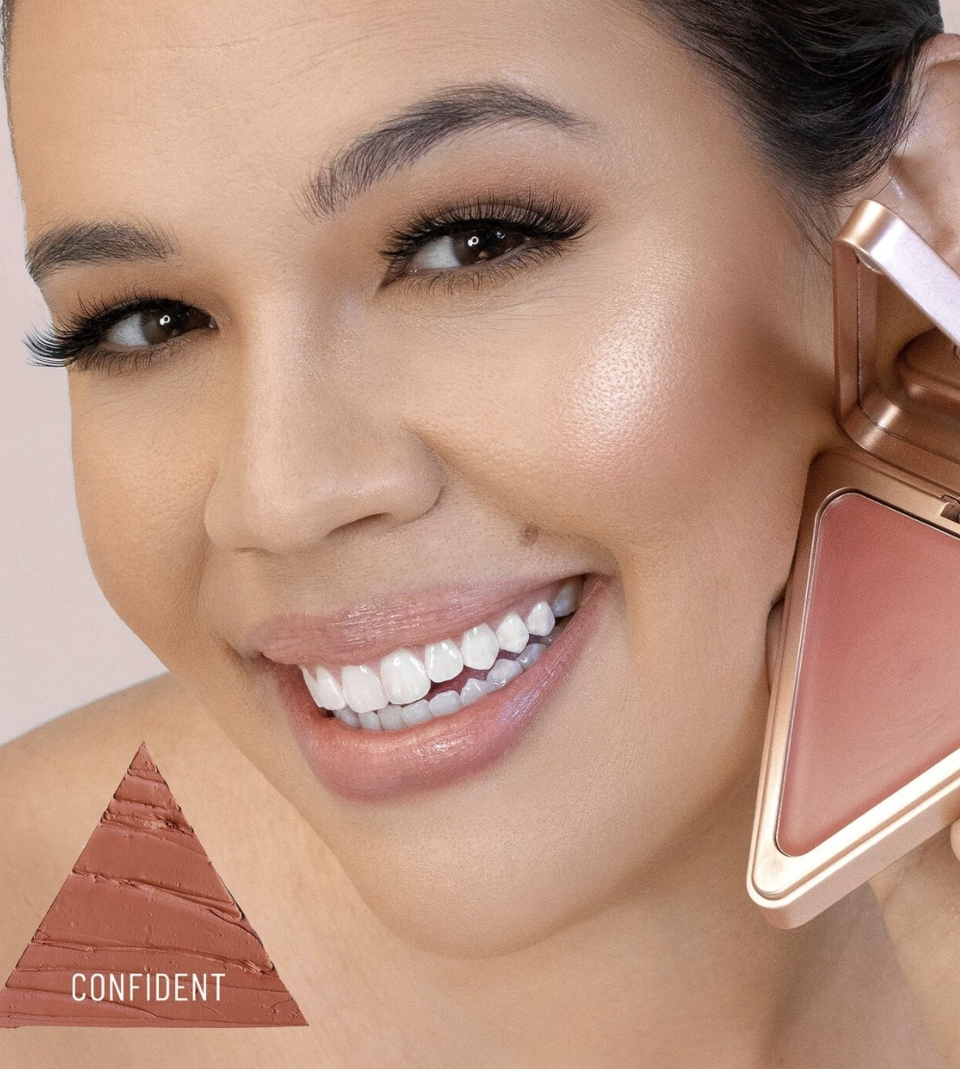 """An adult is smiling while holding up the triangular shaped blush up to their cheek, and there is a triangular texture shot that says """"CONFIDENT"""" in the bottom left corner"""